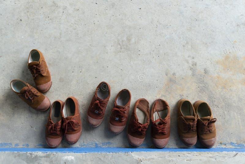 Παπούτσια μαθητών στο τσιμεντένιο πάτωμα στοκ εικόνα