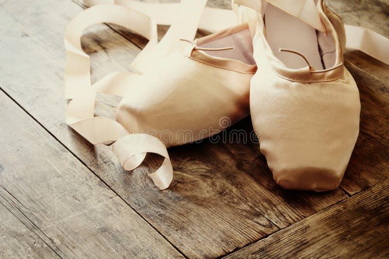 παπούτσια μεταξιού pointe στο ξύλινο πάτωμα φιλτραρισμένος και τονισμένος στοκ φωτογραφία