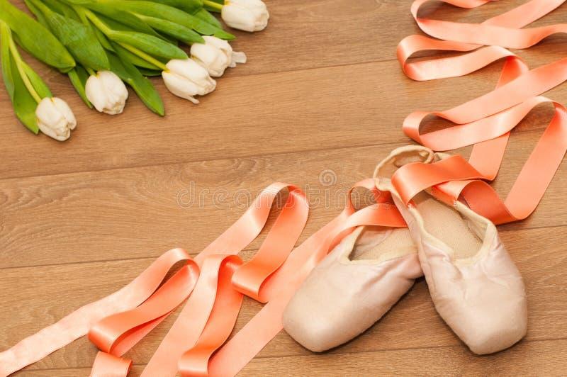 Παπούτσια μπαλέτου pointe και άσπρες τουλίπες στο ξύλινο υπόβαθρο στοκ εικόνες