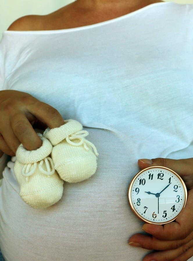 Παπούτσια μωρών ` s, έγκυος κοιλιά και σημειώνοντας ρολόι στοκ φωτογραφίες