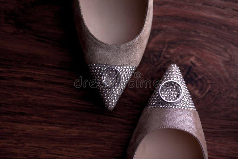 Παπούτσια μόδας νυφών με τους πολύτιμους λίθους με τα γαμήλια δαχτυλίδια στο ξύλινο υπόβαθρο Τοπ όψη Επίπεδος βάλτε στοκ φωτογραφία