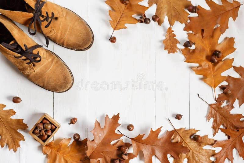 Παπούτσια μόδας πιπεροριζών σουέτ με τα κίτρινα πεσμένα δρύινα φύλλα στο άσπρο ξύλινο υπόβαθρο Τοπ άποψη με Copyspace στοκ φωτογραφία με δικαίωμα ελεύθερης χρήσης