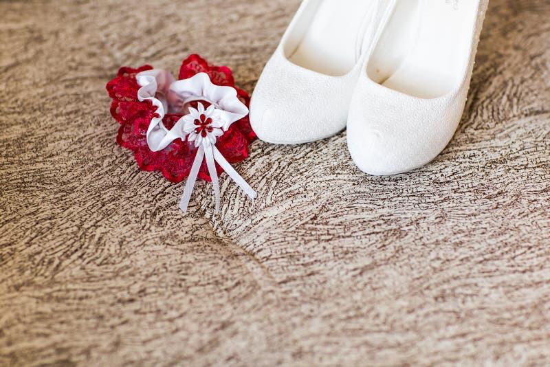Παπούτσια νύφης και κόκκινο γαμήλιο garter στοκ εικόνα με δικαίωμα ελεύθερης χρήσης
