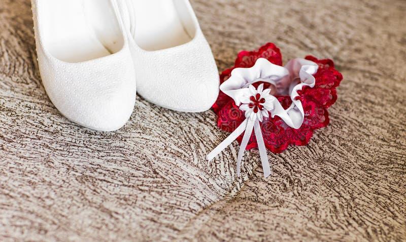 Παπούτσια νύφης και κόκκινο γαμήλιο garter στοκ φωτογραφίες