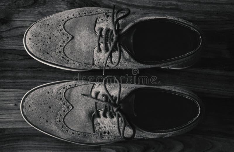 Παπούτσια ξοντρών παπούτσεων των ατόμων δέρματος στο πάτωμα μαύρος & άσπρος στοκ φωτογραφίες