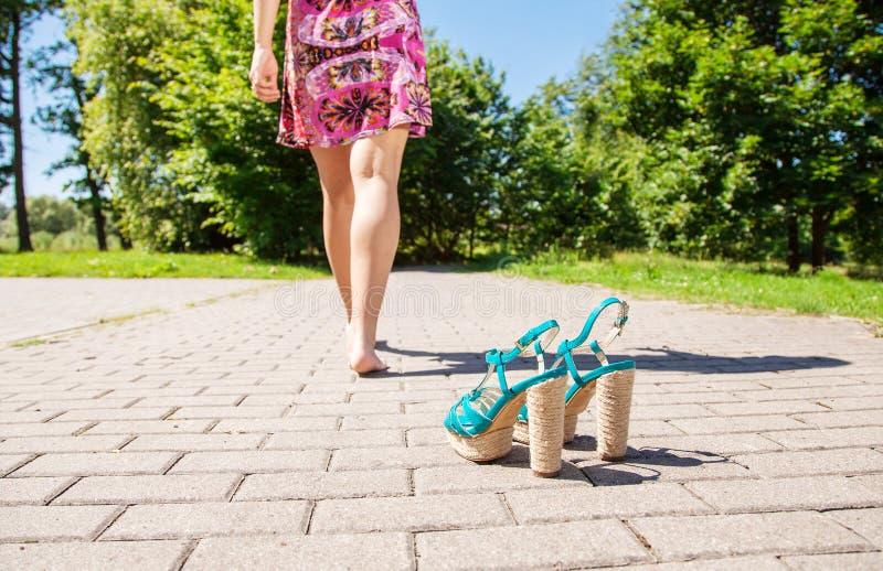 Παπούτσια που στέκονται στο πεζοδρόμιο και τα θηλυκά πόδια που πηγαίνουν μακριά στοκ φωτογραφία
