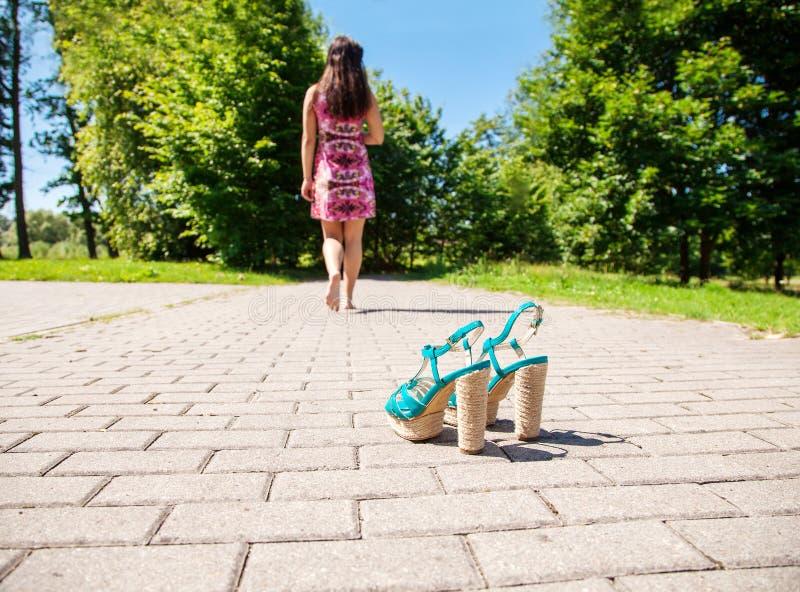 Παπούτσια που στέκονται στο πεζοδρόμιο και τη γυναίκα που πηγαίνουν μακριά στοκ φωτογραφίες