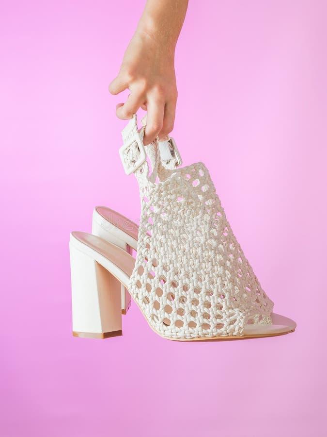 Παπούτσια των θερινών γυναικών εκμετάλλευσης χεριών σε ένα πορφυρό υπόβαθρο στοκ εικόνα με δικαίωμα ελεύθερης χρήσης