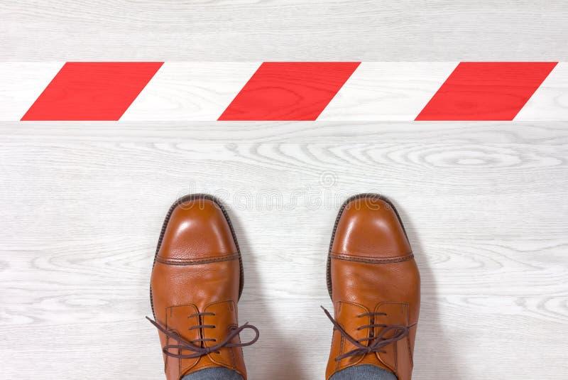 Παπούτσια των κλασικών ατόμων μπροστά από μια κόκκινη και άσπρη γραμμή συντηρήσεων έξω στοκ εικόνα