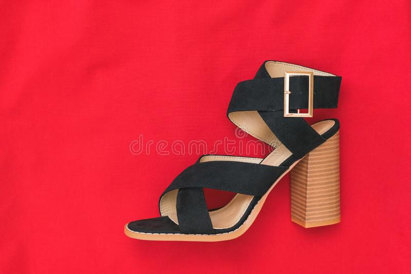 Παπούτσι σουέτ των αριστερών γυναικών σε ένα υπόβαθρο του φωτεινού κόκκινου υφάσματος r στοκ εικόνα