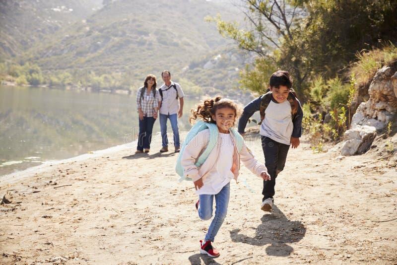 Παππούδες και γιαγιάδες με το τρέξιμο του πεζοπορώ εγγονιών στα βουνά στοκ φωτογραφίες με δικαίωμα ελεύθερης χρήσης