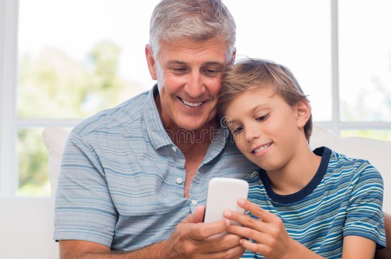Παππούς και εγγονός με το κινητό τηλέφωνο στοκ εικόνες