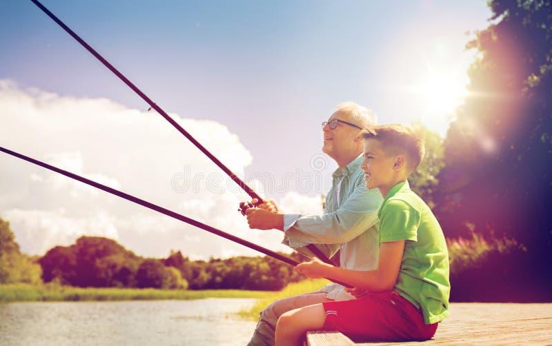 Παππούς και εγγονός που αλιεύουν στο αγκυροβόλιο ποταμών στοκ εικόνες
