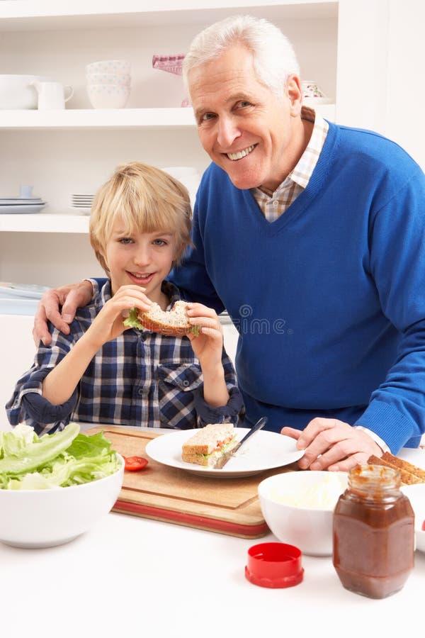 Παππούς και εγγονός που κατασκευάζουν το σάντουιτς στοκ εικόνες