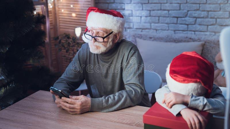 Παππούς και εγγονός στα καπέλα Άγιου Βασίλη ` s τη νύχτα στο σπίτι Το Granddad είναι στο τηλέφωνο, το αγόρι κοιμάται στοκ φωτογραφίες με δικαίωμα ελεύθερης χρήσης