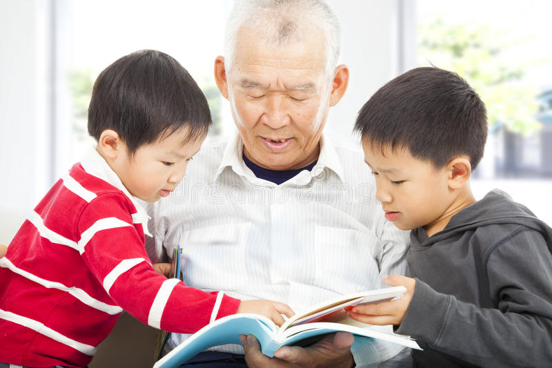 Παππούς και εγγόνια που διαβάζουν ένα βιβλίο στοκ φωτογραφία