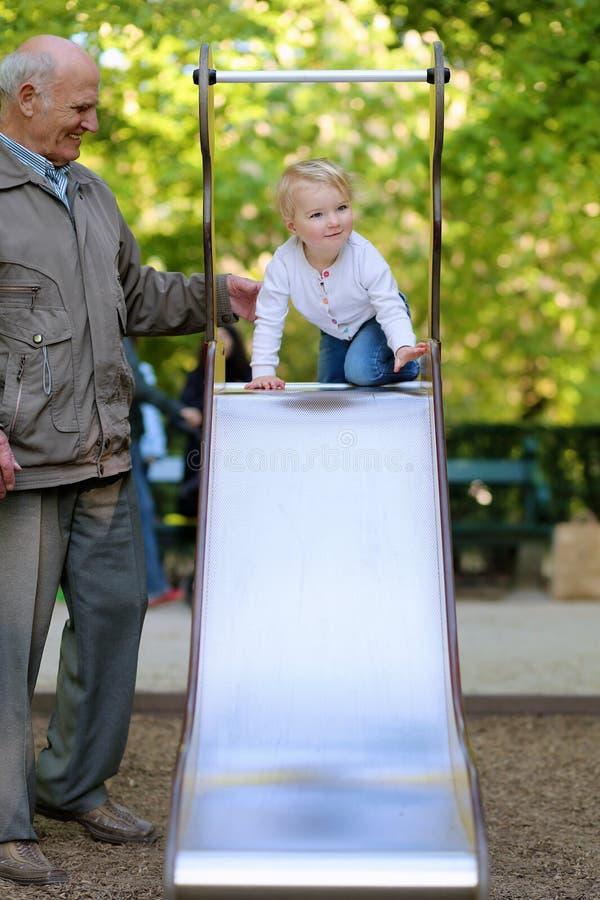 Παππούς με την εγγονή στην παιδική χαρά στοκ φωτογραφία με δικαίωμα ελεύθερης χρήσης