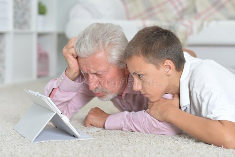 Παππούς με τον εγγονό που χρησιμοποιεί την ταμπλέτα στο πάτωμα στοκ εικόνα
