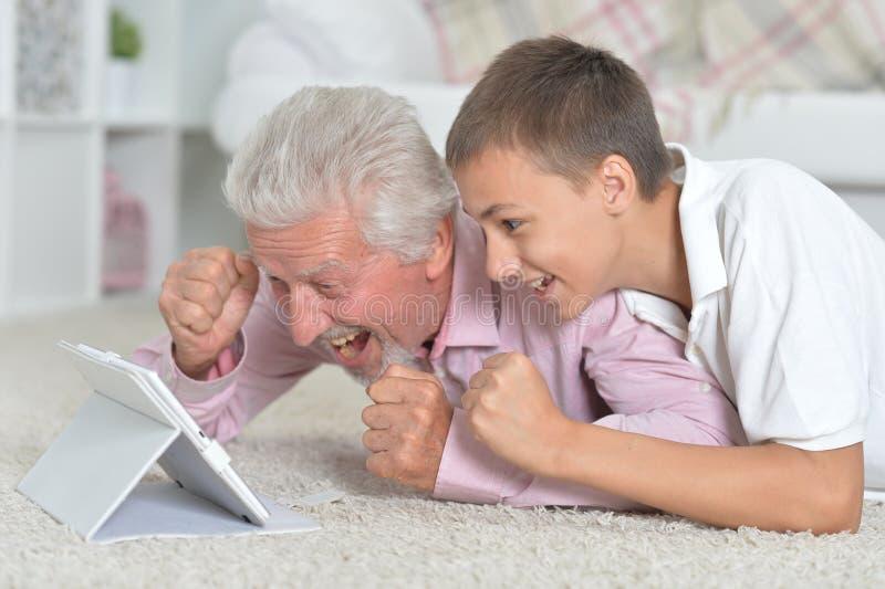 Παππούς με τον εγγονό που χρησιμοποιεί το lap-top στο πάτωμα στοκ φωτογραφίες