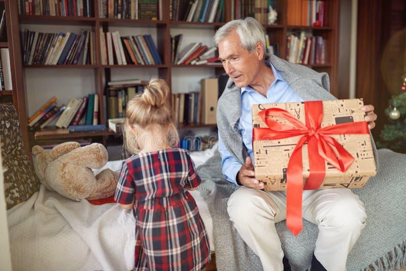 Παππούς που δίνει το χρόνο Χριστουγέννων παρόντος και εορτασμού με τη μικρή εγγονή του στοκ εικόνες