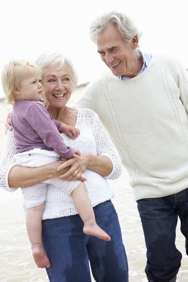 Παππούδες και γιαγιάδες και εγγονή που περπατούν κατά μήκος της παραλίας από κοινού στοκ εικόνες