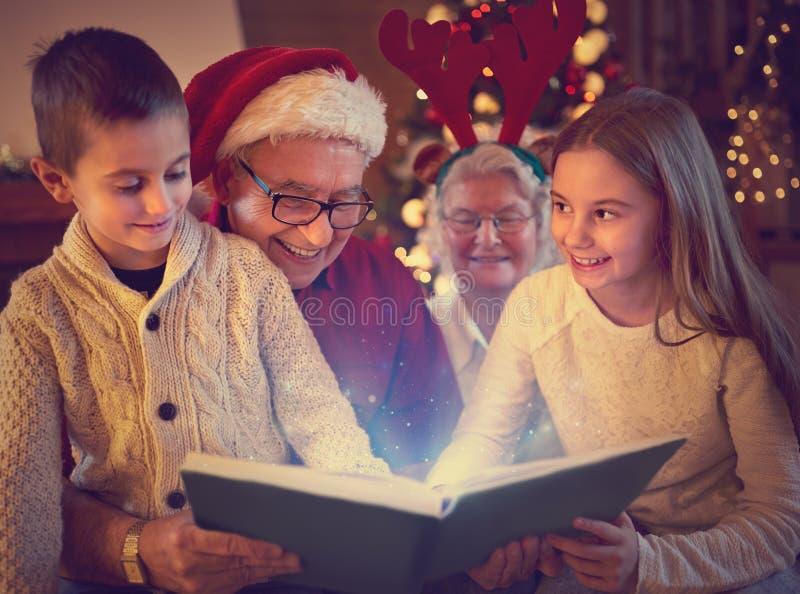 Παππούδες και γιαγιάδες και εγγόνια που διαβάζουν το βιβλίο Χριστουγέννων στοκ εικόνα με δικαίωμα ελεύθερης χρήσης