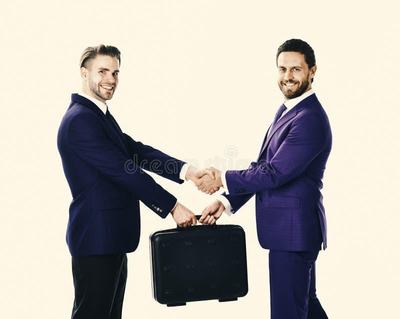 Παράδοση της βαλίτσας στα χέρια των συνεργατών στο άσπρο υπόβαθρο στοκ φωτογραφία με δικαίωμα ελεύθερης χρήσης