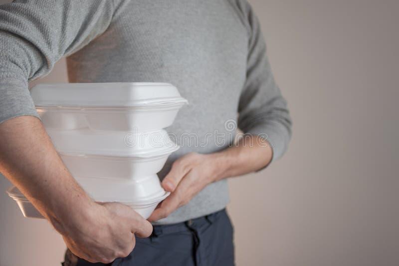 Παράδοση τροφίμων Το άτομο αγγελιαφόρων που κρατά ένα εμπορευματοκιβώτιο των τροφίμων στοκ εικόνα