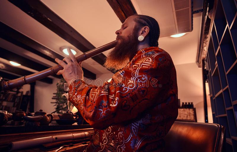 Παράδοση, υγεία, αρμονία Κινεζική τελετή τσαγιού Ο κύριος τσαγιού στο κιμονό αποδίδει στο σκοτεινό δωμάτιο με ένα ξύλινο εσωτερικ στοκ φωτογραφίες με δικαίωμα ελεύθερης χρήσης