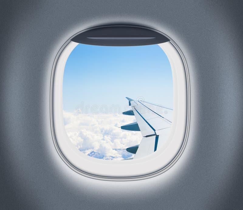 Παράθυρο αεροπλάνων ή αεροπλάνων με το φτερό και το νεφελώδη ουρανό πίσω στοκ φωτογραφία με δικαίωμα ελεύθερης χρήσης
