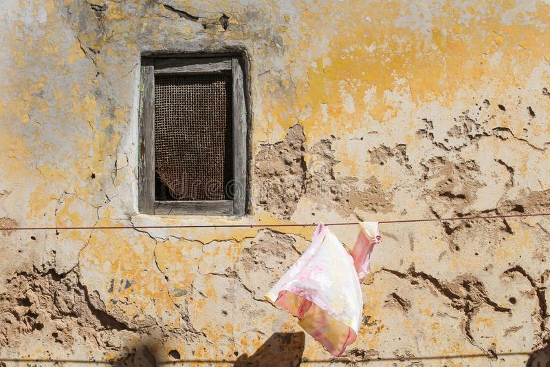 Παράθυρο διεξόδων και μια παλαιά χαλασμένη πρόσοψη στοκ εικόνα με δικαίωμα ελεύθερης χρήσης