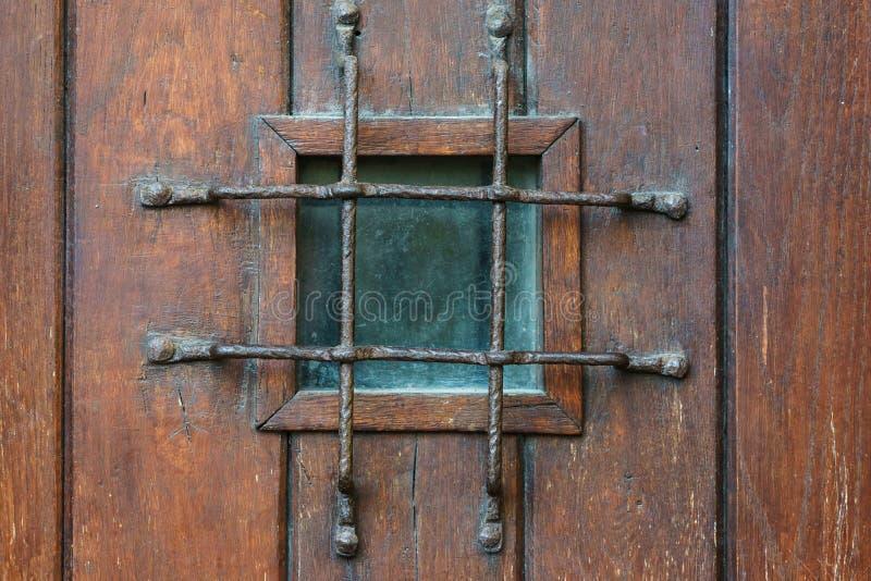 Παράθυρο με τη σχάρα στην παλαιά ξύλινη πόρτα στοκ φωτογραφίες