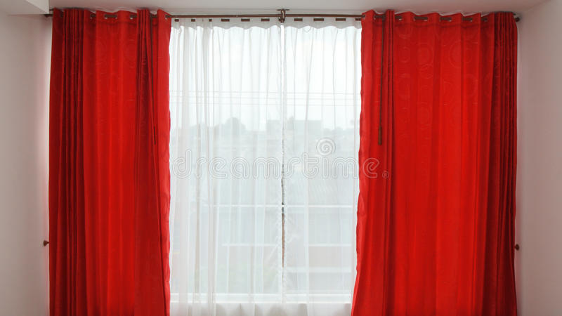 Παράθυρο με τις κόκκινες κουρτίνες ανοικτές στοκ φωτογραφίες