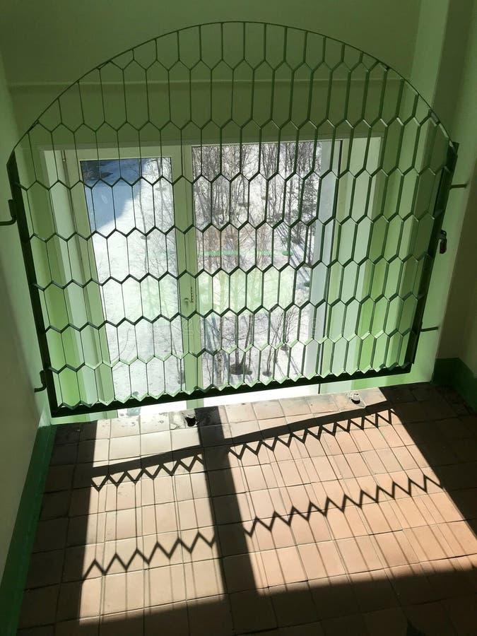 Παράθυρο πίσω από τη λογαριασμένη σχάρα με μορφή μιας αψίδας και τα κύτταρα με μορφή επιμηκυμένων κυττάρων στοκ φωτογραφία με δικαίωμα ελεύθερης χρήσης