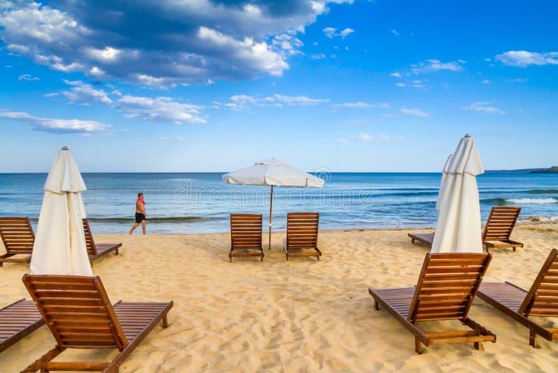 Παράκτιο τοπίο - το άτομο περιφέρεται κατά μήκος της θάλασσας ενάντια στις ομπρέλες και τους αργοσχόλους παραλιών υποβάθρου στοκ εικόνα με δικαίωμα ελεύθερης χρήσης