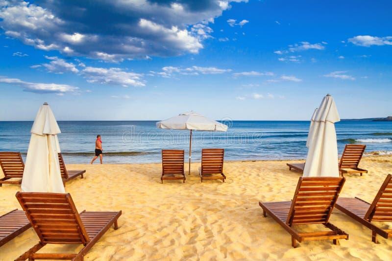 Παράκτιο τοπίο - το άτομο περιφέρεται κατά μήκος της θάλασσας ενάντια στις ομπρέλες και τους αργοσχόλους παραλιών υποβάθρου στοκ φωτογραφία