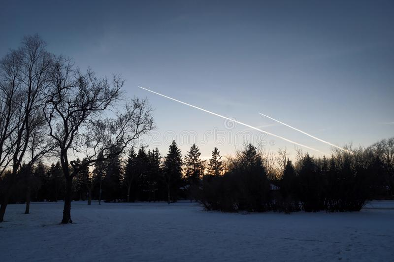 παράλληλοι Ίχνη αεριωθούμενων αεροπλάνων στον ουρανό βραδιού του χειμερινού πάρκου Πάρκο του Frederick Heubach, Winnipeg, Manitob στοκ φωτογραφίες με δικαίωμα ελεύθερης χρήσης