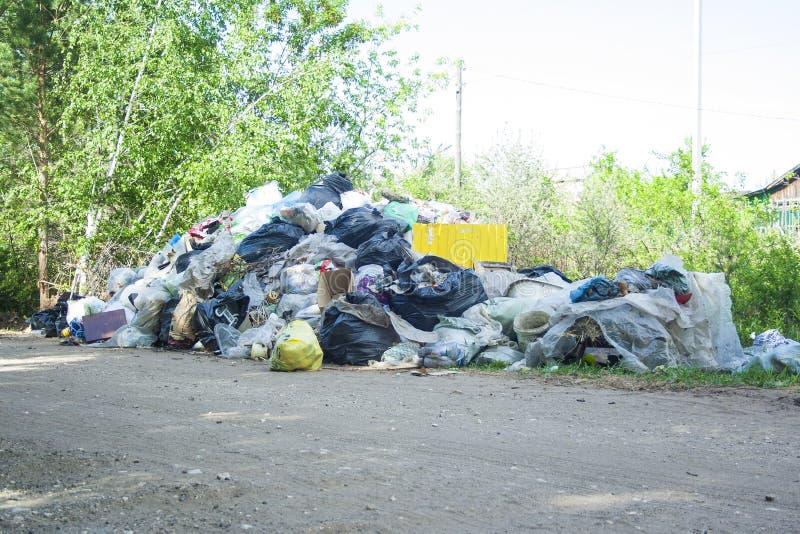 Παράνομη απόρριψη κοντά στο δρόμο άμμου χωρών στη χώρα την ηλιόλουστη ημέρα Ρύπανση απορριμμάτων στη φύση Βρώμικη απόρριψη κοντά  στοκ εικόνα με δικαίωμα ελεύθερης χρήσης