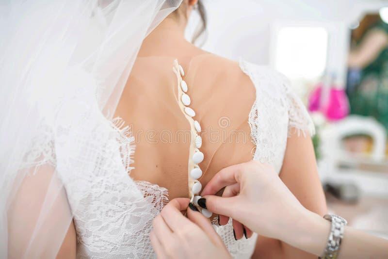 Παράνυμφος ή κορίτσι της τιμής που βοηθά τη νύφη που κουμπώνει επάνω το δαντελλωτός κεντημένο άσπρο φόρεμα στην πλάτη στοκ φωτογραφία