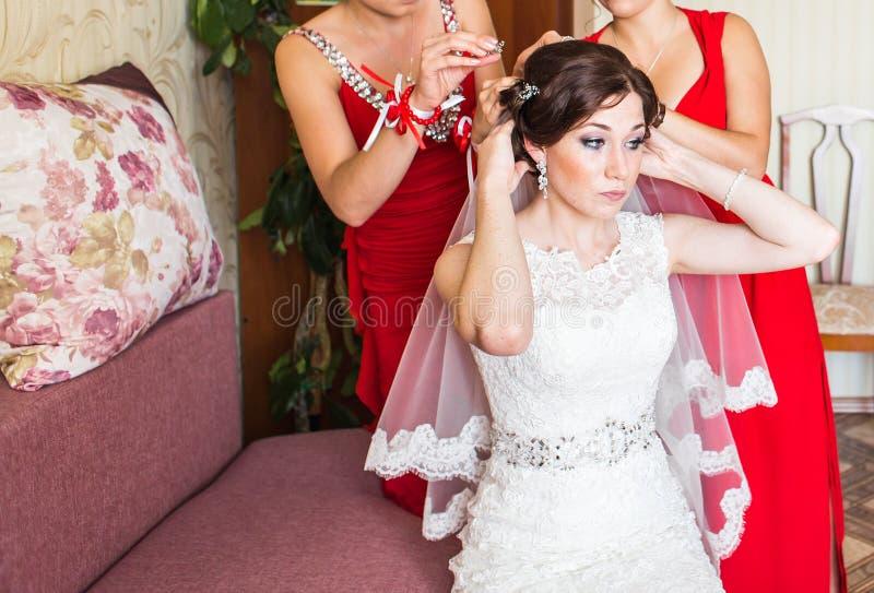 Παράνυμφος που βοηθά τη νύφη με το πέπλο στοκ εικόνα με δικαίωμα ελεύθερης χρήσης