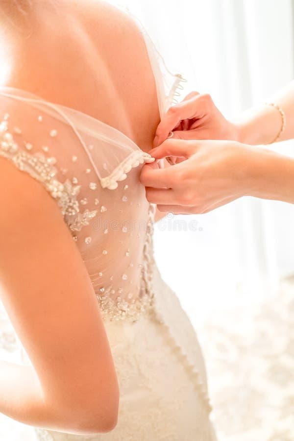 Παράνυμφος που κουμπώνει το φόρεμα στη νύφη το πρωί πριν από την τελετή στοκ φωτογραφία