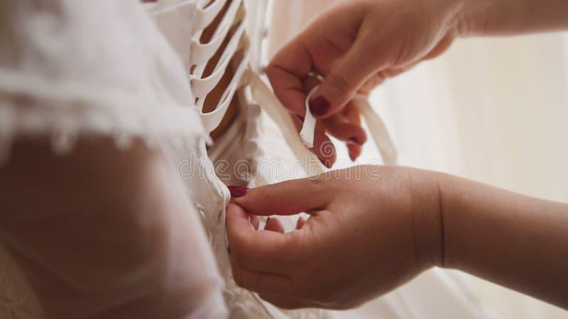 Παράνυμφος που κουμπώνει το φόρεμα στο σπίτι νυφών ` s στοκ εικόνες