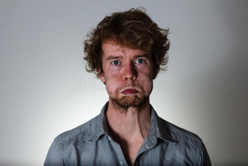 Παράξενη έκφραση νεαρών άνδρων στο γκρίζο υπόβαθρο στοκ φωτογραφίες