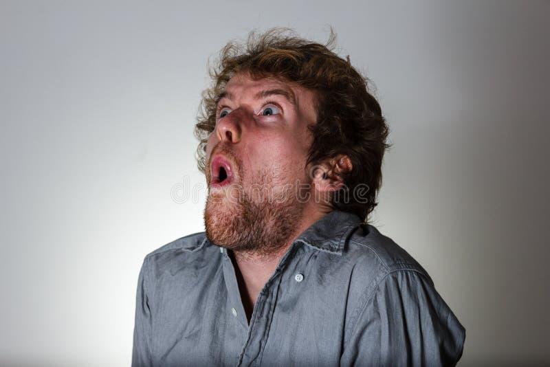 Παράξενος αστείος θρήνος νεαρών άνδρων στο γκρίζο υπόβαθρο στοκ φωτογραφία με δικαίωμα ελεύθερης χρήσης