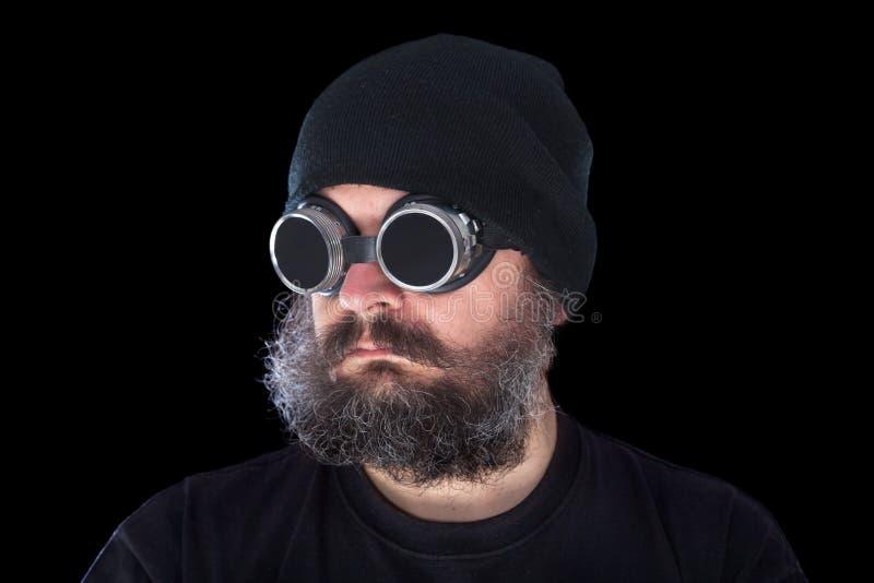 Παράξενος τύπος με τα εκλεκτής ποιότητας προστατευτικά δίοπτρα συγκόλλησης στο μαύρο υπόβαθρο στοκ εικόνα με δικαίωμα ελεύθερης χρήσης