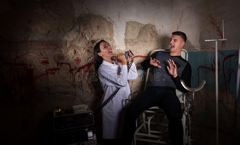 Παράφρων θηλυκός επιστήμονας που κρατά τις ηλεκτρικές συγκλονίζοντας συσκευές μέσα στοκ εικόνα