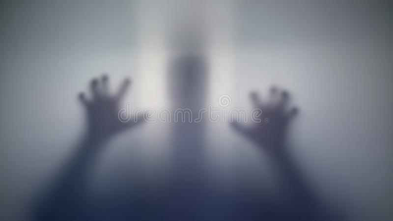 Παράφρων σκιαγραφία προσώπων που εκφοβίζει το θύμα του, παράξενο πλάσμα, τρελλοί άνθρωποι στοκ φωτογραφία