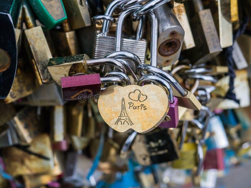 «Παρίσι» που χαράσσεται στην κλειδαριά αγάπης στην κινηματογράφηση σε πρώτο πλάνο των κλειδαριών αγάπης στη γέφυρα του Παρισιού στοκ εικόνες