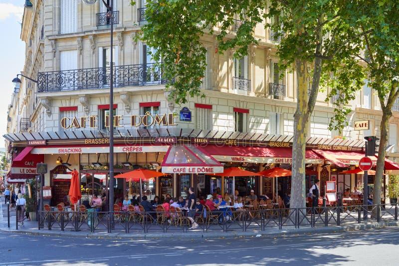 Παρίσι, χαρακτηριστικό brasserie καφέδων με τους πίνακες πεζοδρομίων με τους ανθρώπους και τους τουρίστες που κάθονται σε μια ηλι στοκ φωτογραφία