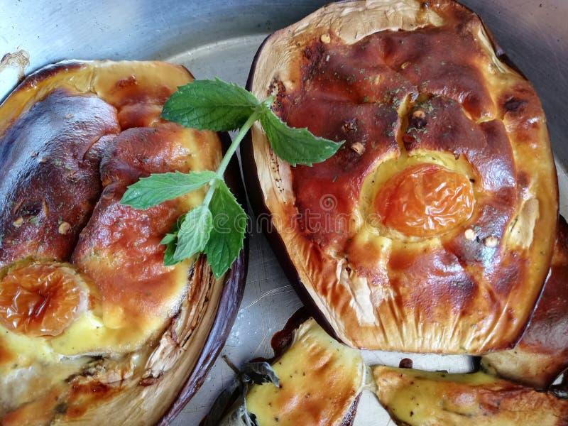 Παραγεμισμένη μπλε μελιτζάνα με τυρί και αυγά διακοσμημένα με ντομάτες κεράσι και κλαδάκια, φυσική μέντα ψημένη στον φούρνο, χρυσ στοκ εικόνες με δικαίωμα ελεύθερης χρήσης